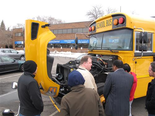 Students examining the engine of a bus