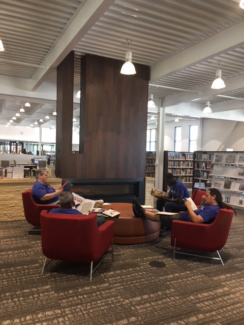 Students sitting in library chairs reading.