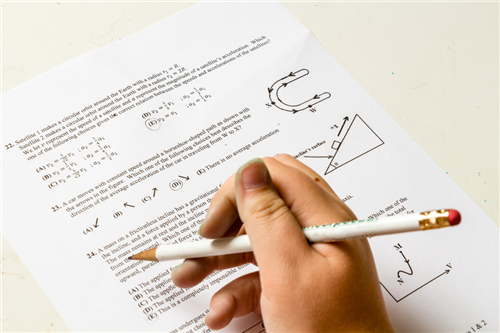 Picture of person holding a pencil working on math