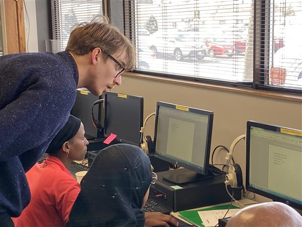 volunteer helping students in computer lab