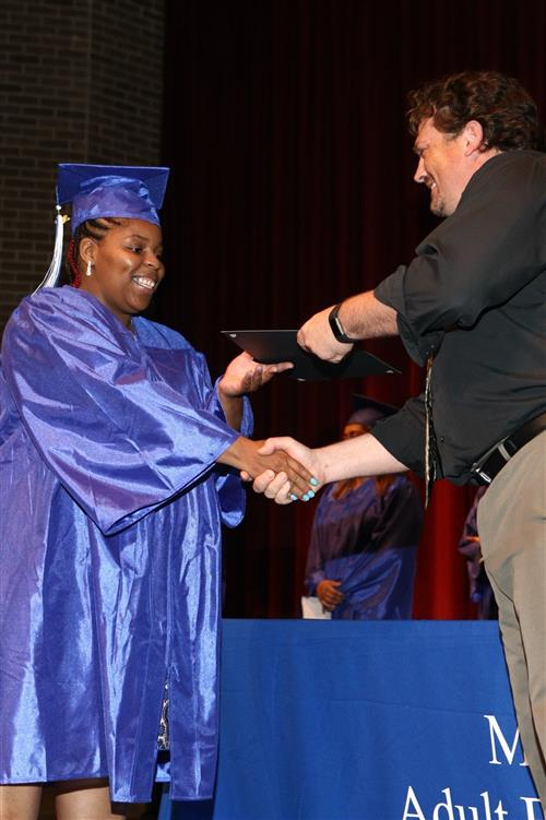 Student receiving her diploma and shaking hands with school administrator.