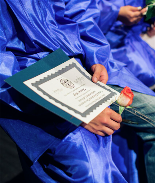 Graduate holding diploma and rose